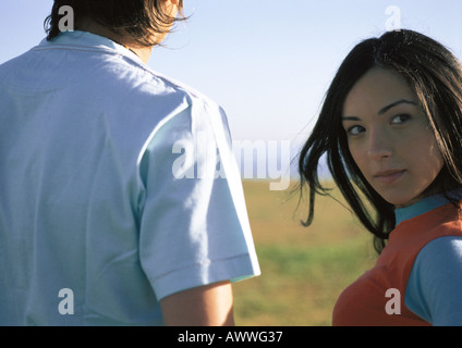 Young woman outdoors with friend, looking at camera, close up - Stock Photo