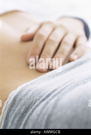 Woman's hand on bare stomach, close-up - Stock Photo