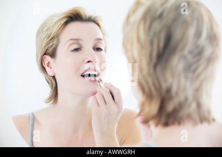 A woman applying lipstick in the mirror - Stock Photo