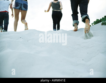 Four people running on sand, low section, rear view - Stock Photo