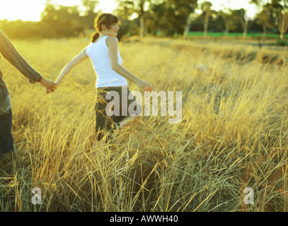 Couple walking in field of tall grass - Stock Photo