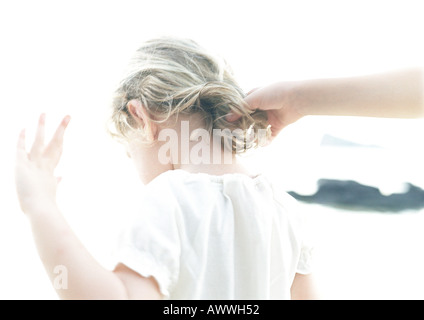 Hand touching child's hair, rear view, blurred - Stock Photo
