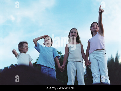 Children holding hands outdoors, one pointing, one shielding eyes, front view - Stock Photo
