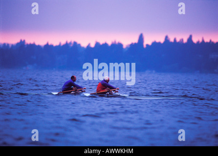 Two middle aged men row a two man shell in rough water at dawn Lake Washington Seattle - Stock Photo