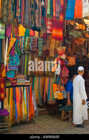 Vertical close up of a man in a white kaftan standing outside a colourful textile shop on Rue Souk Smarine in Marrakesh. - Stock Photo