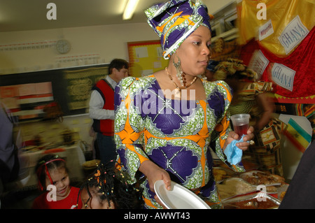Woman in traditional African dress waiting for food to be served at her childrens primary school, West London, Britain, - Stock Photo