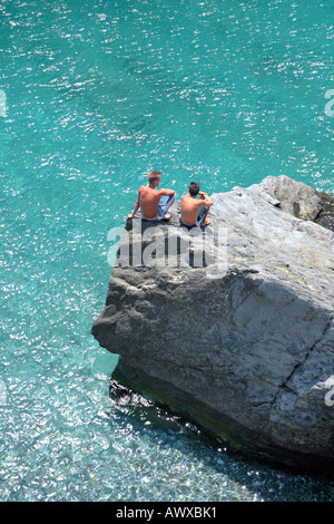 Aerial photo of two young boys sitting on rock looking into deep blue ocean - Stock Photo