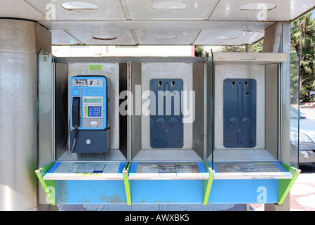 Vandalised phone booth in Spain with just one telephone still intact and working - Stock Photo