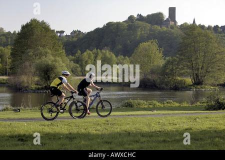 mountainbiker at bicycle lane, castle Blankenstein in background, Germany, North Rhine-Westphalia, Ruhr Area, Bochum
