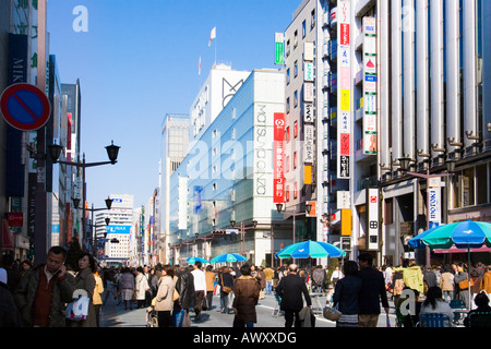 People walking and shopping along Chuo Dori street on Sunday in upscale Ginza district of Tokyo Japan - Stock Photo