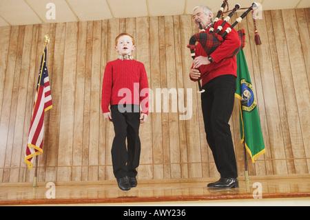 Young boy dancing to bagpipe music - Stock Photo