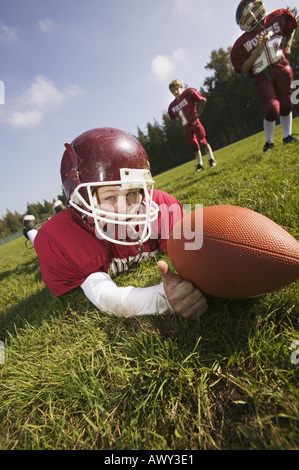 Young football player on the ground - Stock Photo
