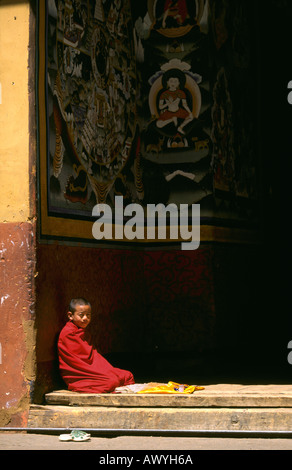 Portrait of a monk kneeling by a doorway in the lower courtyard inside the Ringpun Dzong in Paro, Bhutan. - Stock Photo