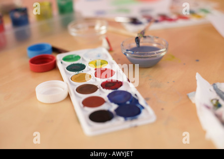 Color palette and painting implements on a table - Stock Photo