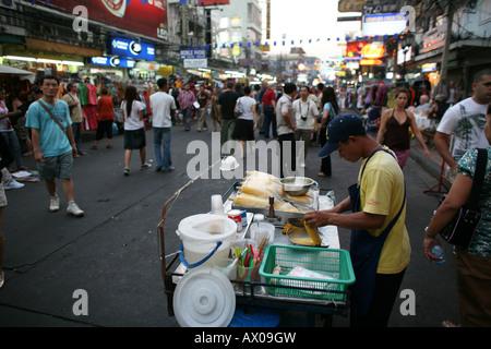 A man sells corn on the cob on a street in Bangkok - Stock Photo
