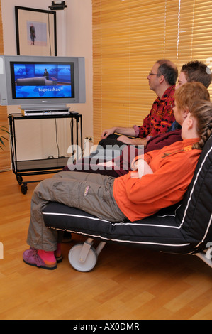 Family sitting on couch watching TV - Stock Photo
