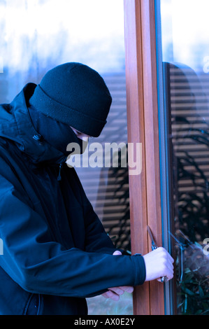 Youth breaking-and-entering using a knife to open patio doors - Stock Photo