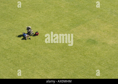 Man lying next to baby carriage on big lawn - Stock Photo