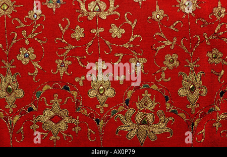 Woven and embroidered textile with golden threads on a red groundcloth Sumptuous textile from Sumatra Indonesia - Stock Photo
