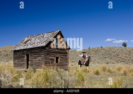 Cowboy with horse at old barn, wildwest, Oregon, USA - Stock Photo
