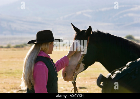 Cowgirl caressing horse, Oregon, USA - Stock Photo
