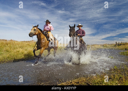 Cowboy and cowgirl riding in water wildwest, Oregon USA - Stock Photo
