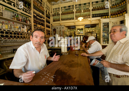 Waiter Fernando sums up the bill on the counter with chalk in El Rinconcillo, a typical Spanish bar in Sevilla, - Stock Photo