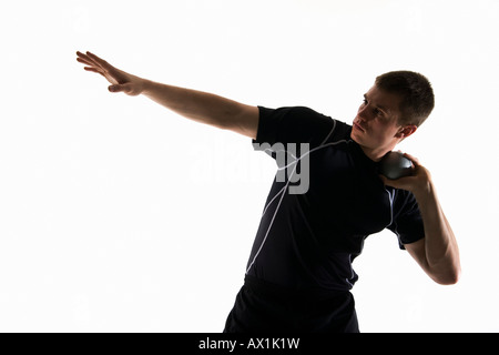 Studio shot of a male track and field athlete holding a shot put ball - Stock Photo