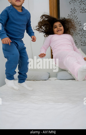 Two children jumping on a bed - Stock Photo