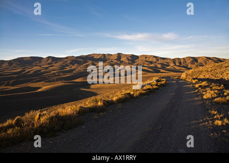 Pass road at hill landscape in the first morning light, Central Andes, Argentina, South America - Stock Photo