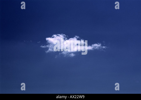 A single cloud sitting on in the sky on a warm hot blue meditteranean day - Stock Photo