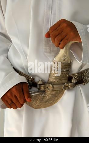 Kanjhar, traditional dagger, worn on a the national dress Dishdash, Sultanate of Oman - Stock Photo