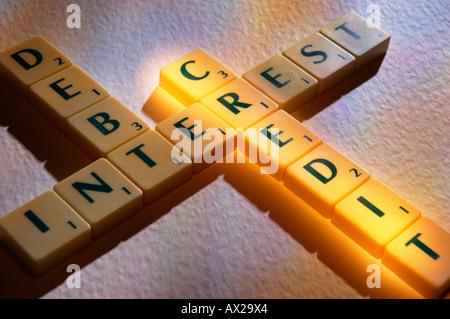 SCRABBLE BOARD GAME LETTERS SPELLING DEBT INTEREST CREDIT - Stock Photo