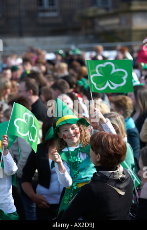 young girl in fancy dress irish costume waving flag in the crowd at the concert and carnival in custom house square - Stock Photo