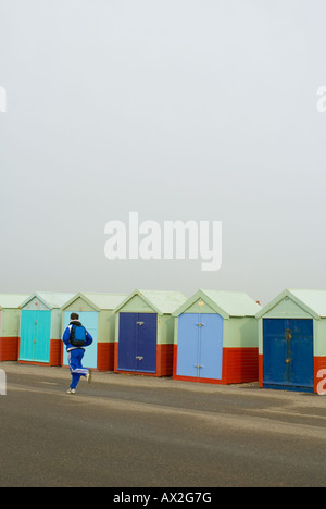 A jogger runs past a row of blue beach huts on the esplanade at Brighton & Hove, Sussex. - Stock Photo