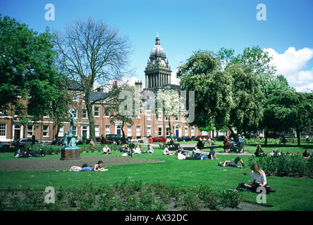 Leeds city hall behind Park Square in Leeds city centre, West Yorkshire, England. Office workers on lunch break. - Stock Photo