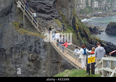 People crossing the Carrick-a-rede rope bridge near Ballintoy in County Antrim , Northern Ireland - Stock Photo