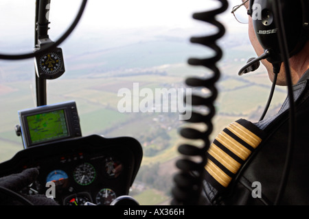 Helicopter pilot flying over countryside in Wiltshire, UK - Stock Photo