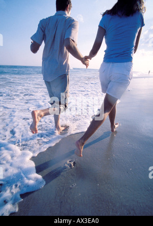 Couple on beach running over water edge - Stock Photo
