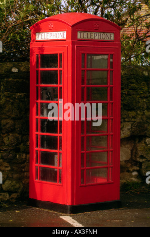 a traditional old style old fashioned type telephone box kiosk painted red with glass windows - Stock Photo