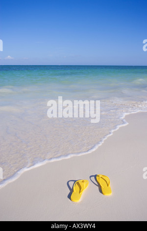 pair of yellow flip flop sandals on beach at waters edge in the Caribbean - Stock Photo