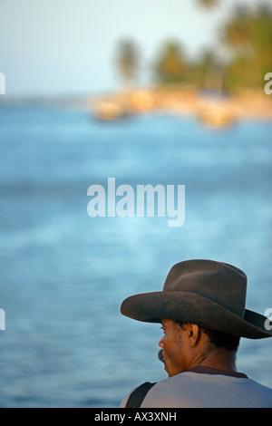 Brazil, Bahia, Boipeba Island, Tinhare Archipelago. A fisherman sits watching the channel dividing Tinhare and Boipeda - Stock Photo