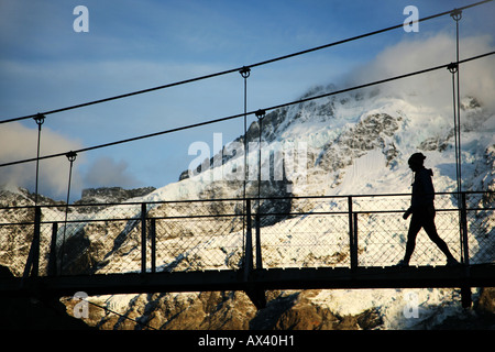 Trekker crossing over the Hooker River in the shadow of Mount Cook, Southern Alps, South Island, New Zealand - Stock Photo