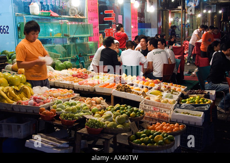 China, Shanghai. Outdoor fruit market and dining area. - Stock Photo