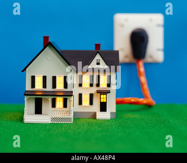 Miniature House Plugged into Electric Socket - Stock Photo
