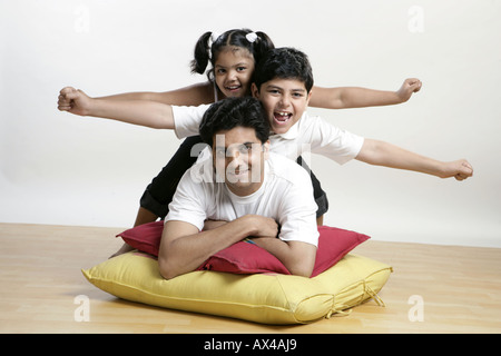 Portrait of a father playing with his children and smiling - Stock Photo