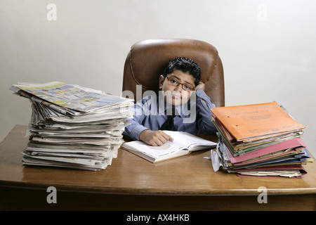 Portrait of a boy working in office and looking tired - Stock Photo