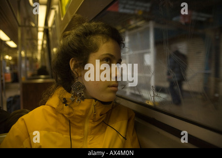 Young woman looks out subway window in an above ground station in Brooklyn New York - Stock Photo