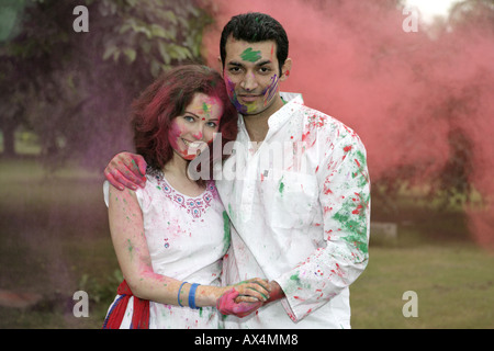 Portrait of a couple playing holi in a park - Stock Photo