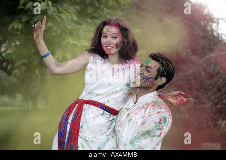 Portrait of a couple playing holi and dancing in a park - Stock Photo